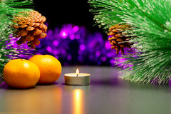 Christmas theme. Burning tea candle and  two mandarins between branches of larch with pine cone Royalty Free Stock Image