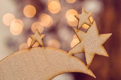 Close up. Christmas wooden toy in the form of stars. Blurry lights of garland on the background. stock photos