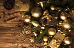 Christmas theme. Christmas decoration in golden and brownish aesthetics with presents in boxes, golden baubles, christmas spices all on a rustic wooden Stock Photo