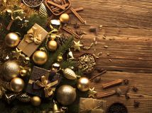 Christmas theme. Christmas decoration in golden and brownish aesthetics with presents in boxes, golden baubles, christmas spices all on a rustic wooden Royalty Free Stock Photography