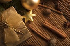 Christmas theme. Christmas decoration in golden and brownish aesthetics with presents in boxes, golden baubles, christmas spices all on a rustic wooden Stock Images