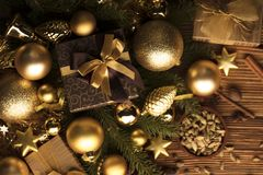 Christmas theme. Christmas decoration in golden and brownish aesthetics with presents in boxes, golden baubles, christmas spices all on a rustic wooden Royalty Free Stock Photo