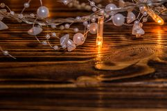 Close up, macro. White beads intertwined with warm lights of Christmas garland. royalty free stock image