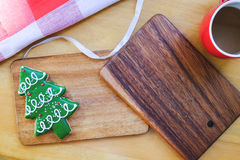 Christmas theme composition. Christmas tree cookie with coffee on wood background Royalty Free Stock Images