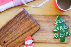 Christmas theme composition. Christmas tree cookie on wood plate with background of paper Santa and coffee mug Royalty Free Stock Images