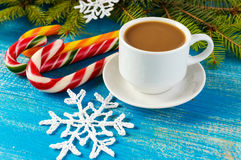 Christmas theme. A cup of coffee with milk cappuccino, in the form of bright candy canes and green spruce branches Royalty Free Stock Photography