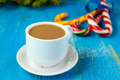 Christmas theme. A cup of coffee with milk cappuccino, in the form of bright candy canes and green spruce branches Stock Images