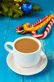 Christmas theme. A cup of coffee with milk cappuccino, in the form of bright candy canes and green spruce branches Stock Photos