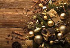 Christmas theme. Christmas decoration in golden and brownish aesthetics with presents in boxes, golden baubles, christmas spices all on a rustic wooden Royalty Free Stock Image