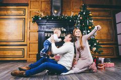 Christmas theme. Father throws the son of blond one year old, sit on a wooden tree in front of Christmas tree with gifts, mom make. S selfie, self-portrait on Royalty Free Stock Images
