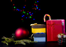 Christmas theme. Fir tree branch, gift boxes, candy cane, red christmas ball on nice background with christmas lights bokeh Royalty Free Stock Photos