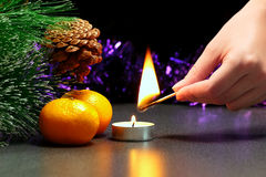 Christmas theme. Hand light a tea candle Royalty Free Stock Photography