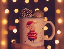 Christmas theme. in the hand of a mug with a pig and Christmas balls. bokeh in the background. Twinkling lights on the holiday royalty free stock photo