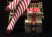 Christmas theme Lady Santa with red and white candy cane stripe stocking legs and gifts Royalty Free Stock Photo