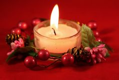 Christmas Theme. A lighted candle with Christmas decorations royalty free stock photography