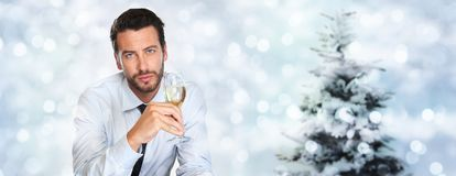 Christmas theme, man drinks a glass of sparkling wine on blurred. Bright lights background Stock Images