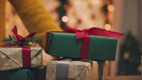 Christmas theme. Young woman puts the gifts under the Christmas tree. In the defocusing. stock video footage