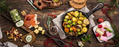 Christmas themed dinner table. Banner of Delicious Christmas themed dinner table with roasted meat steak, appetizers and desserts. Top view. Holiday concept stock photography