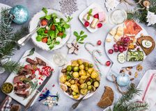 Christmas themed dinner table. Flat lay of delicious Christmas themed dinner table with roasted meat steak, appetizers and desserts. Top view. Holiday concept stock photos