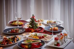 Christmas themed dinner table with a variety of appetizers and salads.  royalty free stock image