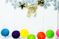 Christmas themed ornaments and colorful ball lights on white clean wood background - with copy space Stock Image