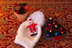 Christmas-themed still life with cute wooden Santa figurine, velvet box shaped as a tree, wooly hat and small planter