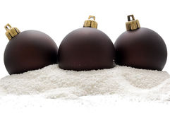 Christmas three deep brown balls in snow stock image