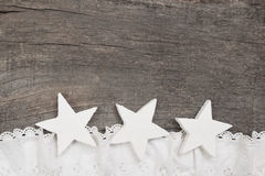 Christmas: three white stars on grey wooden background, lace sno Royalty Free Stock Photo