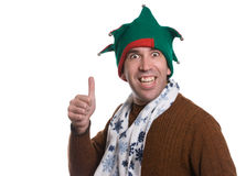 Christmas Thumbs Up. A happy man giving a thumbs up while wearing  an elf hat and a white scarf, isolated against a white background Royalty Free Stock Photos