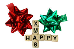 Christmas tiles and rosettes. Tiles spelling happy x-mas with rosettes in red and green Stock Photography