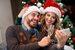 Christmas time – smiling couple taking selfie on Christmas Stock Images