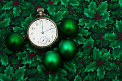 Christmas Time. A pocket watch with green glass balls on a holly berry background, Christmas time Stock Photos