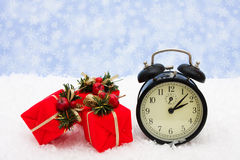 Christmas Time. A black vintage face clock with presents sitting on snow background, Christmas time Stock Image