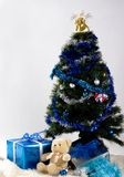 Christmas time. Gifts and teddy bear under christmas tree Stock Photography