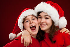 Christmas time. Kids with Santa Claus hat on red background Royalty Free Stock Photo
