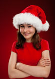 Christmas time. Girl with Santa Claus hat on red background Stock Photography