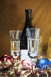 Christmas time. A bottle of wine,two glasses with sparkling wine in it and some christmas decorations on a golden background Stock Photo