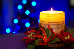 Christmas time. Christmas candle with blurry lights on background Royalty Free Stock Photography