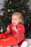 Christmas time. Adorable baby girl with Christmas gift in pajamas in front of tree Royalty Free Stock Photos