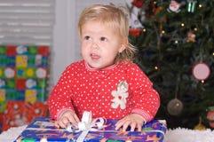Christmas time. Adorable little girl opening Christmas gift wearing pajamas Stock Photo