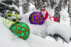 Christmas time. Two color christmas baubles sitting in a bed of snow Royalty Free Stock Photo