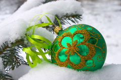 Christmas time. A green christmas bauble sitting in a bed of snow Royalty Free Stock Photos