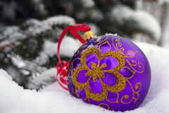 Christmas time. A violet christmas bauble sitting in a bed of snow Stock Photos