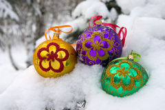 Christmas time. Three color christmas baubles sitting in a bed of snow Stock Image