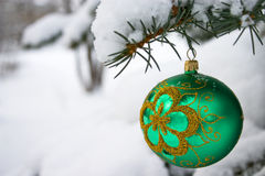 Christmas time. Green  christmas glass ball hanging on the tree in snow Royalty Free Stock Photos