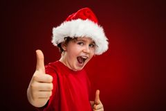 Christmas time - boy with Santa Claus Hat showing ok sign royalty free stock photo