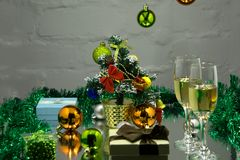 Christmas time and cheers concept. Male and female hands with drinks. Two hands hold glasses of champagne, close up. Man and woman. With Christmas tree on Stock Image