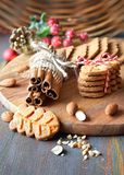 Christmas time, closeup on almond cookies with spices and berrie. Christmas time, closeup on almond cookies with cinnamon sticks, clovers, almonds and berries on royalty free stock images