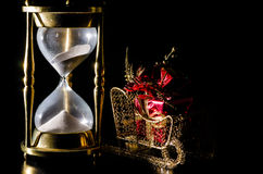 Christmas Time Concept with Hourglass. Christmas gift on sleigh and hourglass on black background.  Concept showing time running out for Christmas shopping Royalty Free Stock Image