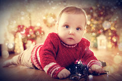 Christmas time. Cute baby crawl on the floor playing with lights Royalty Free Stock Photo